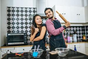 attraktives Paar, das in der Küche zu Hause kocht foto