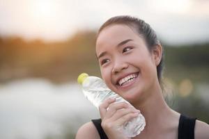 junger Fitness-Teenager, der Wasserflasche nach laufender Übung hält