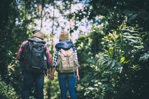 junge aktive Reisende, die Hände halten, während sie im Wald gehen foto
