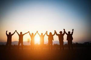 Silhouette des glücklichen Teams, das hohe Hände macht