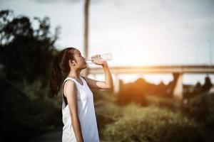 Trinkwasser des jungen Fitness-Teenagers nach laufender Übung foto