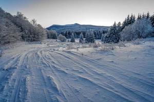 Im Winter schneebedeckte Straße zwischen Bergen