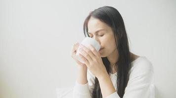 schöne Frau im Bett mit einer Tasse Kaffee liegen