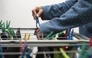 eine Nahaufnahme eines Menschen, der seine frisch gewaschenen Kleider mit Hilfe der bunten Kleiderschneider aufhängt foto
