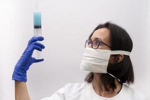 eine Krankenschwester, die eine Maske und Handschuhe trägt und eine Spritze mit einem Virusimpfstoff in einer modernen Klinik hält foto