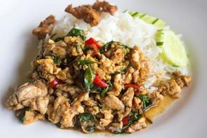 gebratenes Schweinefleisch und Basilikum mit Reis umrühren
