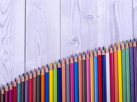 Buntstifte aus Holz, in Form einer Leiter angeordnet, auf grau-weißem Hintergrund. Bildungskonzept.