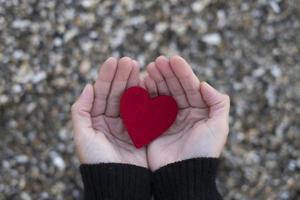 rotes Herz zwischen den Händen einer Frau auf einem Hintergrund von Strandsteinen. Konzept von San Valentine foto