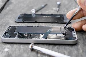 Der Techniker hält einen Schraubenzieher und hält eine Handy-Reparatur-Nahaufnahme im Handy mit einer Fixierbatterie aus einem kaputten Service-Shop-Center auf einem Holztisch. Smartphone repariert Wartungskonzept.