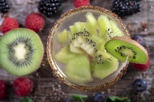 Kiwi-Cocktail von oben gesehen verziert mit Früchten des Waldes auf einem hölzernen Hintergrund