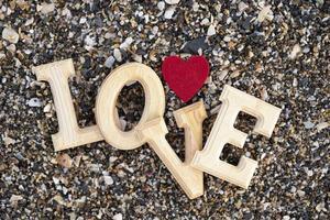 Holzbuchstaben, die das Wort Liebe mit einem roten Herzen auf einem Hintergrund des Strandsandes bilden. Konzept von San Valentine