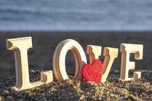 Holzbuchstaben, die das Wort Liebe mit einem roten Herzen an der Küste bilden. Konzept der Liebenden