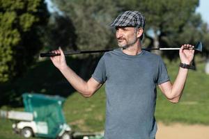 Golfspieler mit einer Kappe, die einen Golfschläger auf seinem Rücken hält