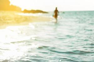 verschwommene Person, die im Wasser am Strand geht