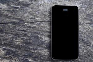 Draufsicht des mobilen Smartphones des schwarzen Bildschirms des Modells auf leerem altem Holztischhintergrund. Draufsicht Telefon flach legen und Platz für Geschäftskonzept kopieren.