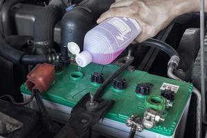 Hände eines Technikers, der der Batterie in einem Servicecenter Wasser hinzufügt