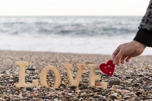 Holzbuchstaben, die das Wort Liebe und eine Hand bilden, die ein rotes Herz an der Küste hält. Konzept von st. Valentinstag