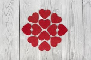 rote Herzen, die eine geometrische Figur in der Mitte eines weißen und grauen hölzernen Hintergrunds bilden. Konzept des Valentinstags