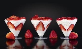 Erdbeeren mit Sahne in der Tasse auf schwarzem Hintergrund foto