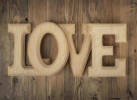 Holzbuchstaben, die das Wort Liebe auf einem Walnussholzhintergrund bilden. Konzept von st. Valentinstag