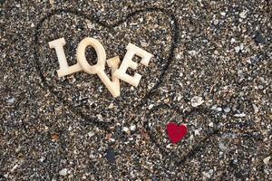 Holzbuchstaben, die das Wort Liebe mit einem roten Herzen auf einem Hintergrund des Strandsandes bilden, innerhalb eines Herzens, das mit den Fingern gemacht wird. Konzept von San Valentine