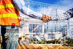 Bauarbeiter geben sich die Hand