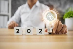 Würfel des Jahres Nummer 2021 auf Holztisch mit Glühbirne