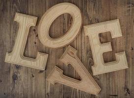 unordentliche Holzbuchstaben, die das Wort Liebe auf einem Walnussholzhintergrund bilden. Konzept von st. Valentinstag