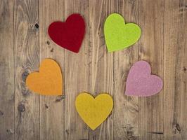 farbige Herzen, die einen Kreis auf einem Walnussholzhintergrund bilden. Konzept von st. Valentinstag foto