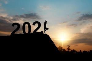 Silhouette des glücklichen neuen Jahres 2021 mit Frau, die Yoga tut