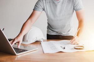 Architekt, der Laptop verwendet, um eine Blaupause zu entwerfen foto