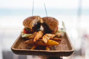 Burger mit Pastetchen und Käse auf braunem Holztablett