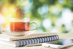 heißes Glas Tee auf Holztisch für die morgendliche Trinkzeit foto