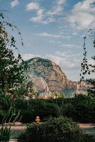 grüne Bäume nahe braunem Berg unter weißen Wolken während des Tages
