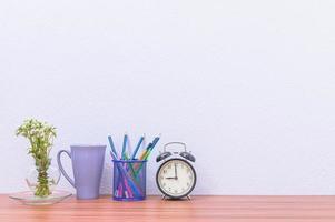Bleistift, Stift und Uhr auf dem Schreibtisch