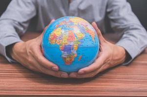 Mann hält einen Globus