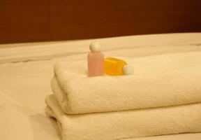 luxuriöses Schlafzimmer mit zwei Handtüchern und Shampoo auf dem Bett