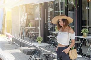 asiatische Frau, die außerhalb eines Cafés aufwirft