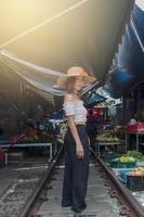 hübsche asiatische Frau, die auf den Bahngleisen aufwirft
