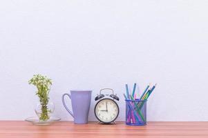 Bleistifte, Kugelschreiber und Uhr auf dem Schreibtisch