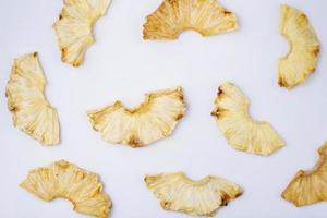 Draufsicht von getrockneten Ananasscheiben auf einem weißen Hintergrund