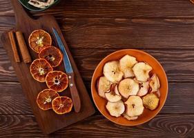 Draufsicht von getrockneten Orangenscheiben mit Küchenmesser auf einem hölzernen Schneidebrett und getrockneten Apfelscheiben auf einem Teller auf hölzernem Hintergrund
