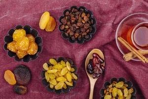 Draufsicht auf getrocknete Früchte Kirschpflaumen Rosinen Aprikosen und getrocknete Datteln in Mini-Torten-Dosen serviert mit Tee auf dunkelrotem Farbhintergrund