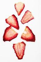 Draufsicht der getrockneten Erdbeerscheiben lokalisiert auf weißem Hintergrund foto