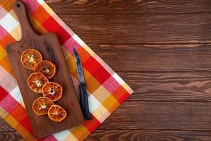 Draufsicht von getrockneten Orangenscheiben mit Küchenmesser auf einem hölzernen Schneidebrett auf hölzernem Hintergrund mit Kopienraum foto