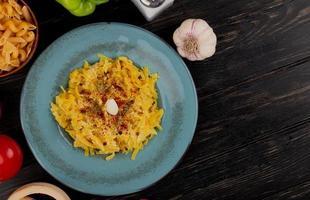 Draufsicht von Makkaroni-Nudeln in Platte mit Tomatenpfeffersalz Knoblauch und Salz auf Holzhintergrund mit Kopienraum foto