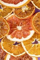 Draufsicht von getrockneten Orangen- und Grapefruitscheiben angeordnet auf lila Hintergrund