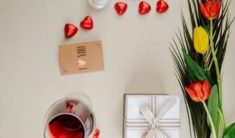 Draufsicht auf einen Strauß Tulpen mit herzförmigen Pralinen, eingewickelt in rote Folie, Glas Wein, kleine braune Papiergrußkarte und eine Geschenkbox auf weißem Hintergrund