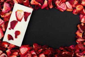 Draufsicht von getrockneten Erdbeerscheiben mit weißem Schokoriegel auf schwarzem Hintergrund