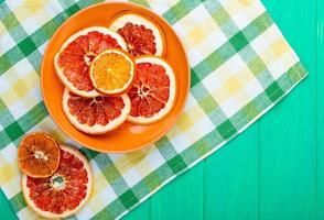 Draufsicht von getrockneten Orangen- und Grapefruitscheiben in einer Platte auf karierter Tischdecke auf grünem hölzernem Hintergrund mit Kopienraum